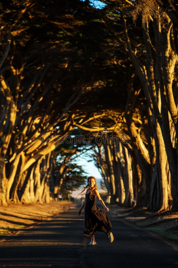 Happy girl in a tunnel with trees stock images