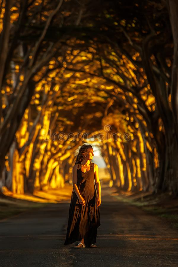 Happy girl in a tunnel with trees royalty free stock photography