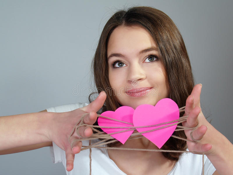 The happy girl with two pink hearts stock photos
