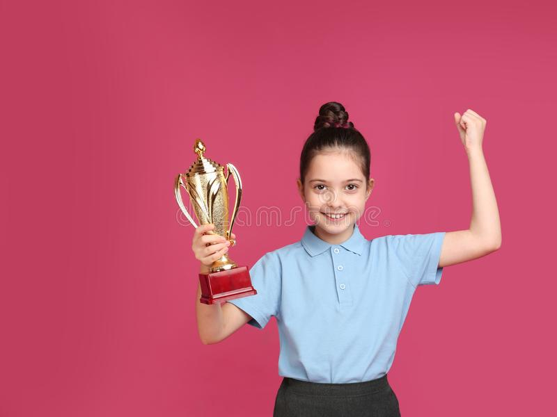 Happy girl in  uniform with golden winning cup on pink background. Space for text. Happy girl in school uniform with golden winning cup on pink background. Space royalty free stock image