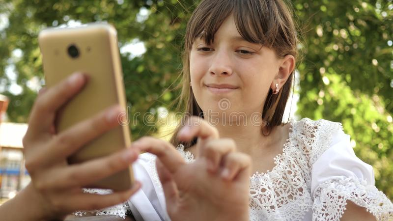 Happy girl using smartphone scrolls through pages in the online store in the park on the bench. Young millennial woman royalty free stock photos