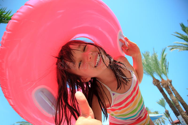 Happy girl on vacation. Happy little girl on vacation holding an inflatable rubber swimming float stock photo