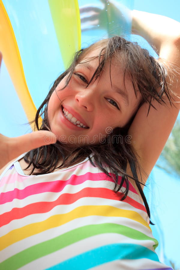 Happy girl on vacation. Portrait of a smiling happy young girl with an inflatable swimming mattress stock images