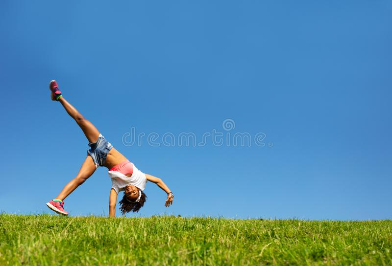Happy girl walk on hands over blue sky and grass stock photography