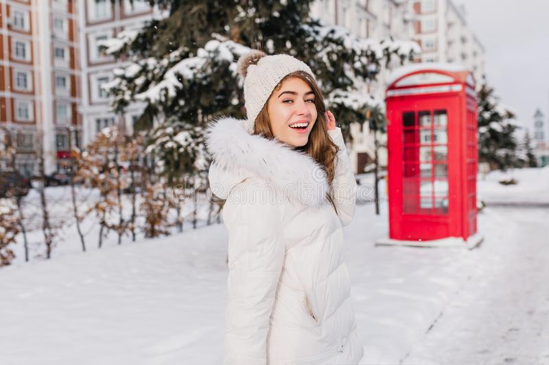 Happy girl walking around in winter sunny morning with smile. Fascinating woman in knitted hat looking over shoulder stock image