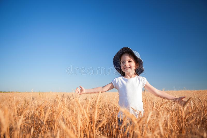 Happy girl walking in golden wheat, enjoying the life in the field. Nature beauty, blue sky and field of wheat royalty free stock images
