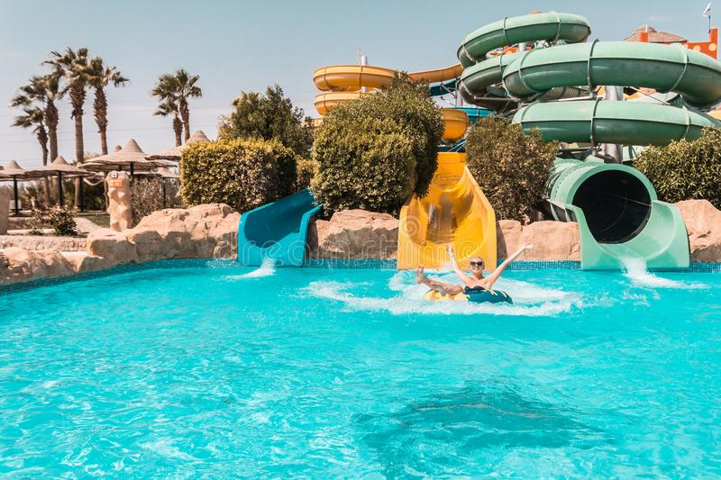 Happy girl on a water slide in the pool, having fun during summer vacation in a beautiful water park. The boy slides along the waterslide and splashes stock photos