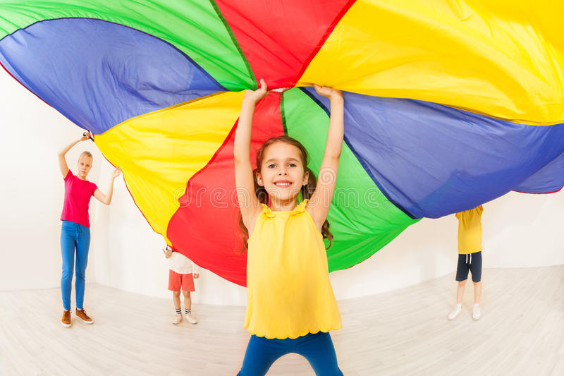 Happy girl waving parachute during sports festival stock photo