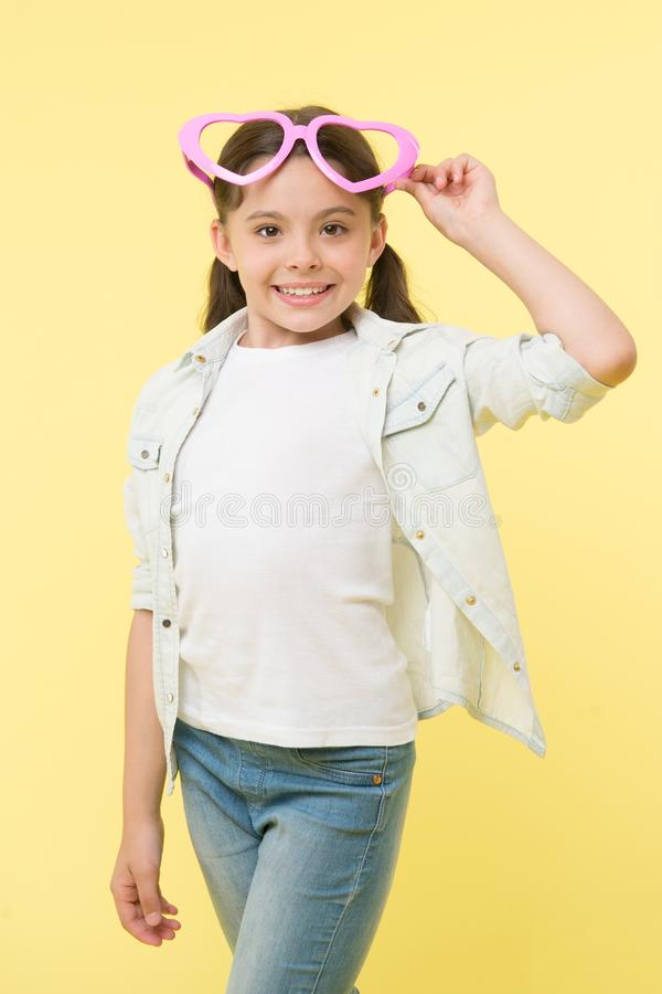 Happy girl wear heart shaped glasses on yellow background. Little child smile in fashion accessory. Funky style beauty royalty free stock photography