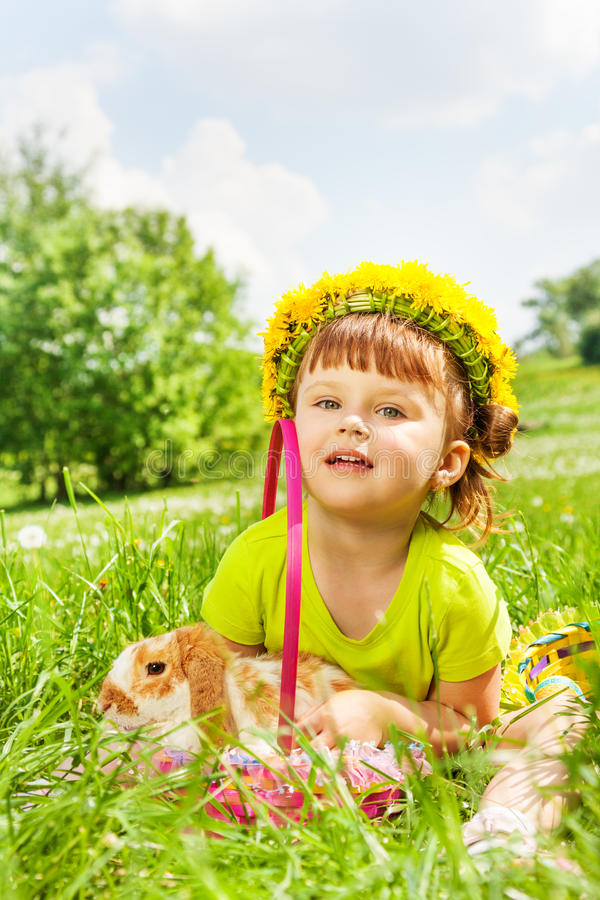 Happy girl wearing flowers circlet and rabbit. Happy girl with flowers circlet with rabbit in the basket sitting in the park in summer royalty free stock photography
