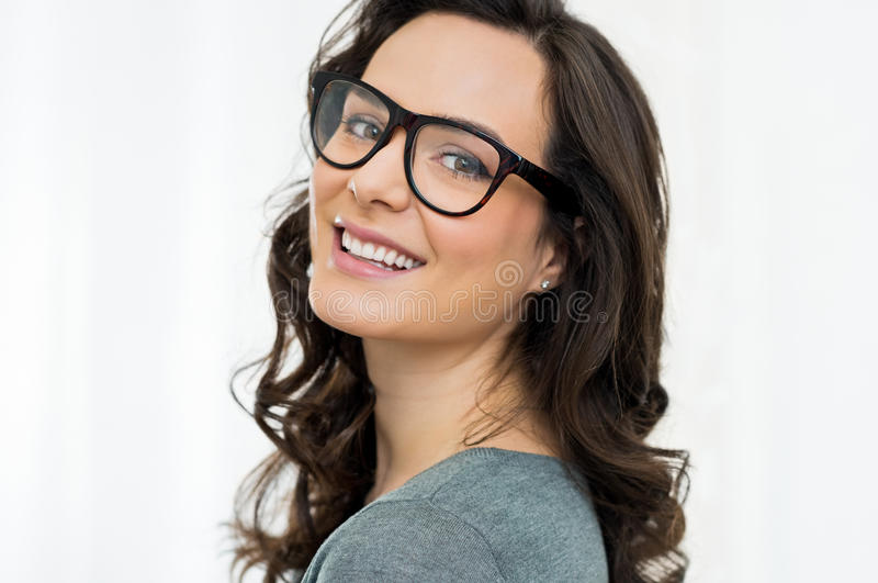 Happy girl wearing glasses. Closeup of smiling young woman looking at camera with eyeglasses royalty free stock photography