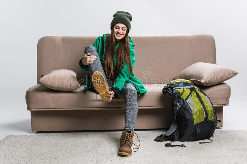 Happy girl wearing hiking boots on sofa. With backpack royalty free stock photography