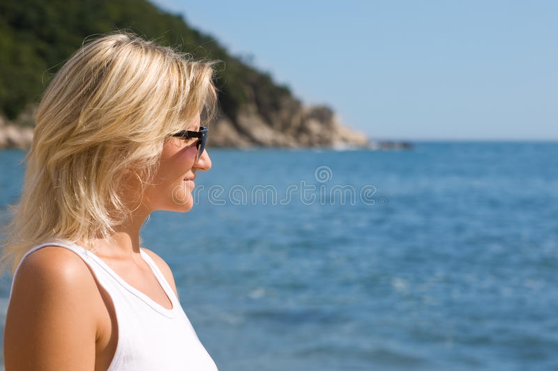 Happy girl wearing sunglasses at the sea. Sunny day royalty free stock images