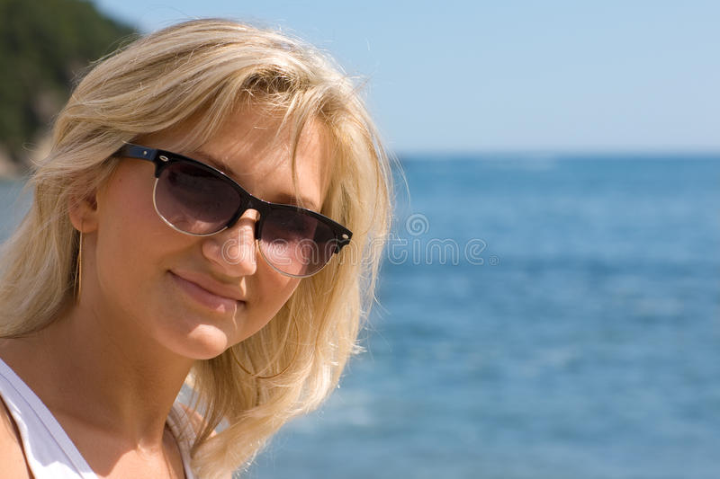 Happy girl wearing sunglasses at the sea. Sunny day stock photography