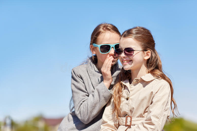 Happy girl whispering secret to her friends ear stock photo