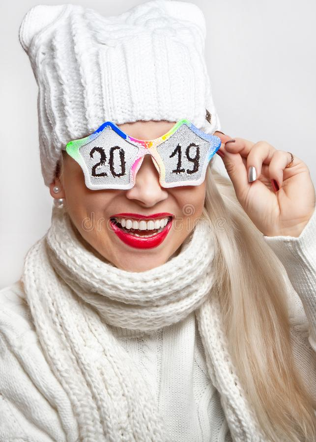 Happy girl in a white hat and scarf, wearing funny glasses with the inscription `2019`. royalty free stock image