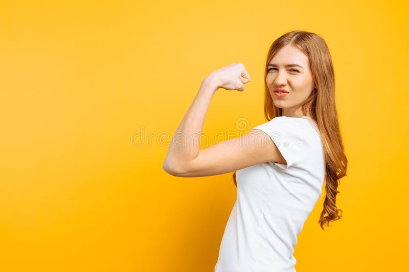 Of happy girl in white t-shirt showing arm muscles on yellow background. Portrait of happy girl in white t-shirt showing arm muscles on yellow background royalty free stock photo