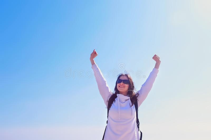 Happy girl winner in victory pose with raising hands on blue sky background. Happy girl winner in sunglasses with backpack stands in victory pose with raising royalty free stock images
