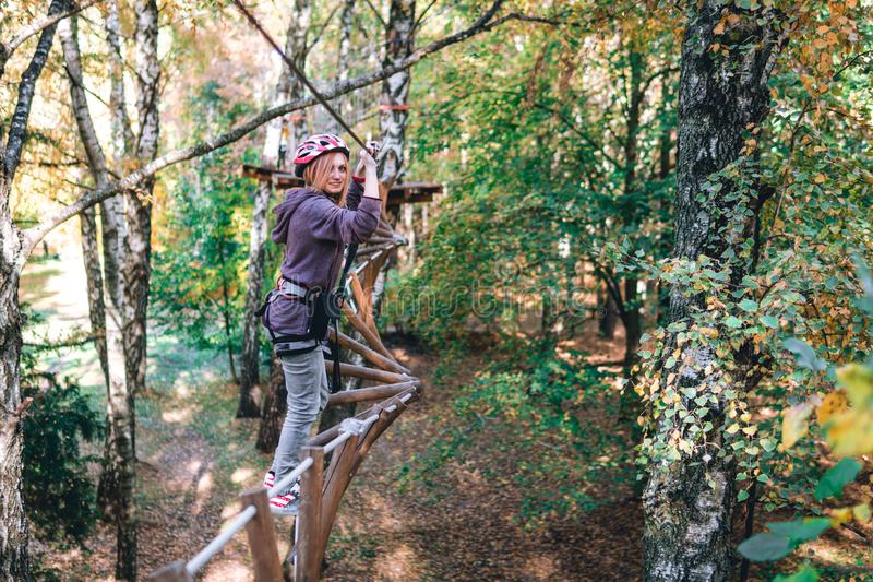 Happy girl, woman, climbing gear in an adventure, rope road, insurance, attraction, amusement park, active recreation, autumn royalty free stock photography