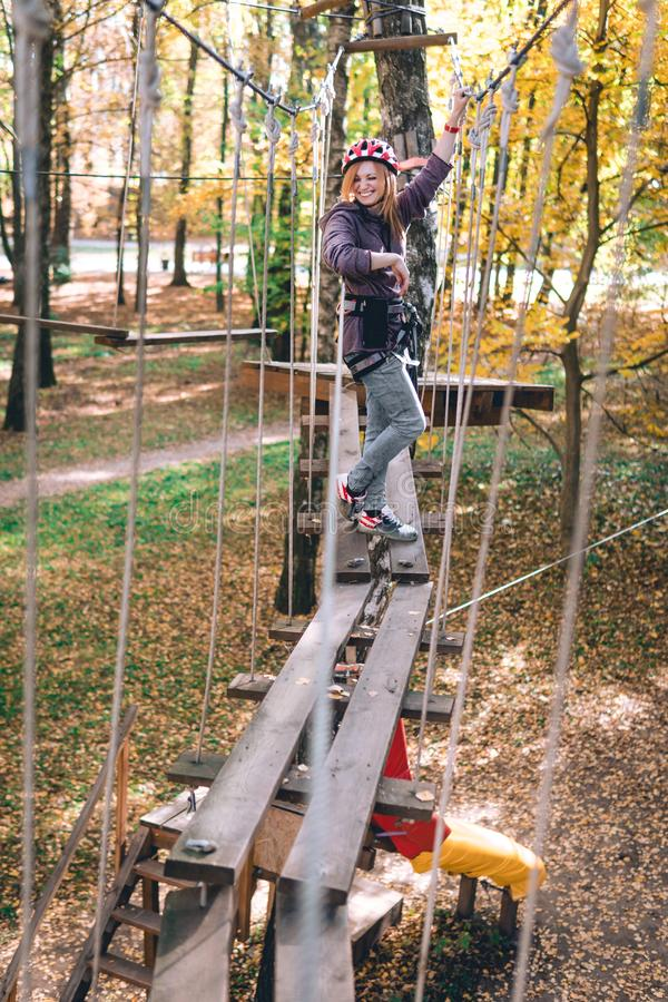 Happy girl, women, climbing gear in an adventure park are engaged in rock climbing on the rope road, arboretum, insurance, royalty free stock photos