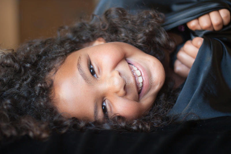Happy girl wrapped in black. Portrait of a happy multi-racial girl laying on bed and wrapped in black material stock photos