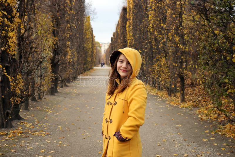 Girl in a yellow hooded coat in the park Augarten Vienna autumn season stock image