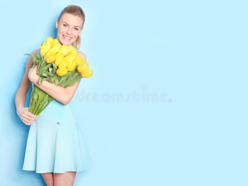 Happy girl with yellow tulips. Blue background royalty free stock photo