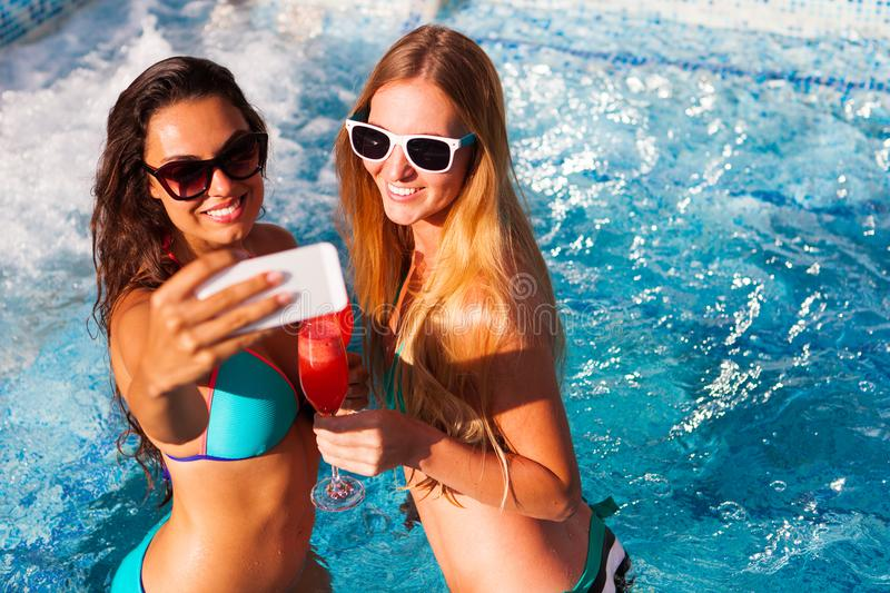 Happy girlfriend with a drink on a summer party by the pool take. Selfie on smartphone royalty free stock photography
