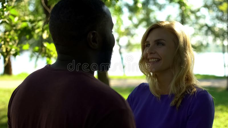Happy girlfriend looking with love at boyfriend, multiracial relationship, care royalty free stock photos