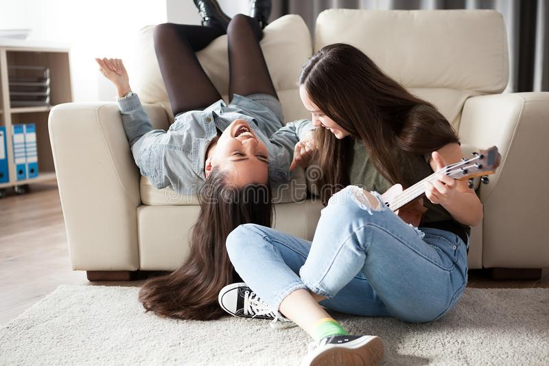 Happy girlfriends spending quality time in the living room stock photography