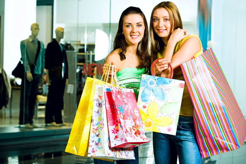 Happy girls. Portrait of two smiling girls wearing casual clothes with paper bags in their hands on the background of boutique�s window royalty free stock photo