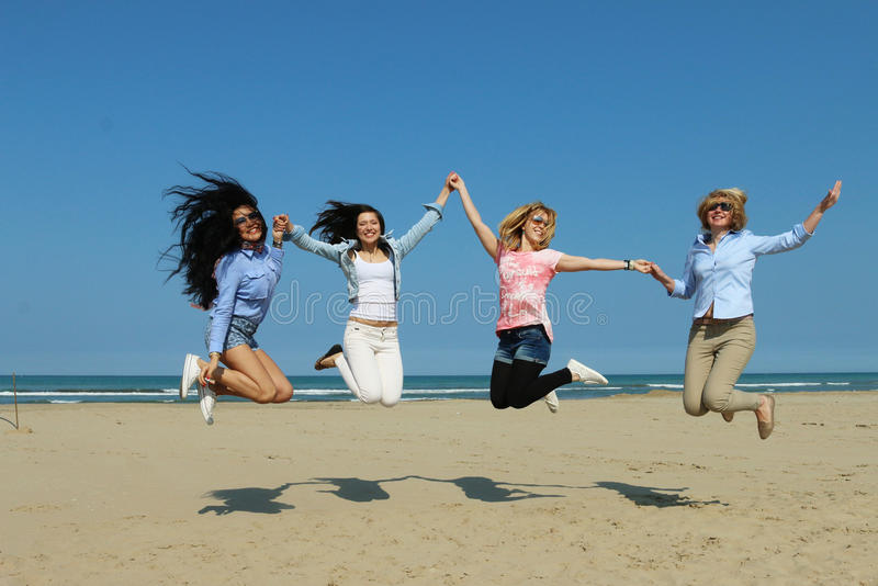 Happy girls on beach jumping together stock photo