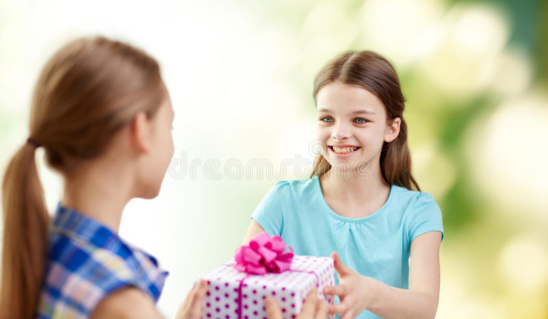 Happy girls with birthday present over green. People, children, holidays, friends and friendship concept - happy little girls with birthday present over green stock photo
