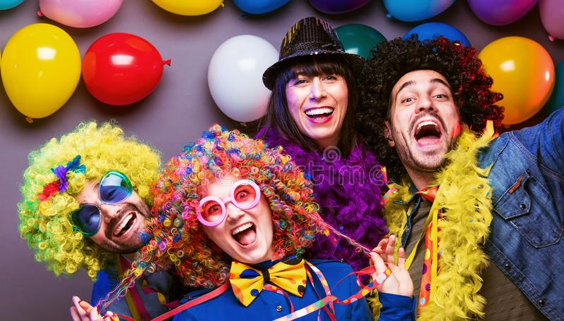 Happy girls and boys at Carnival Party clinking glasses with champagne royalty free stock image