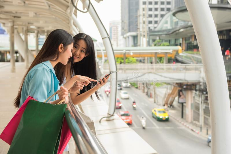 Happy girls check store location by smartphone stock images