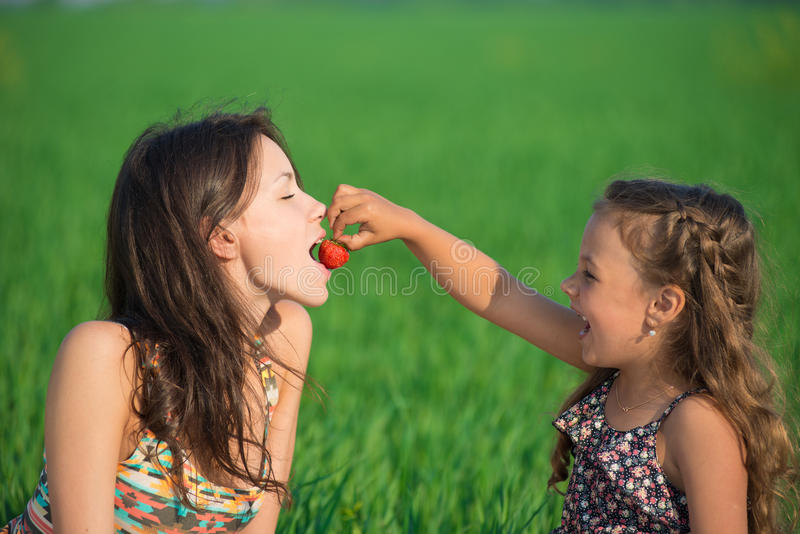 Happy girls eating strawberries on green grass royalty free stock photo