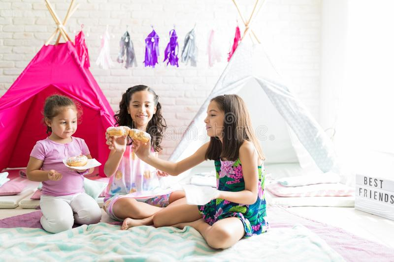 Girls Enjoying Fresh Donuts While Sitting Against Teepee Tents stock photos