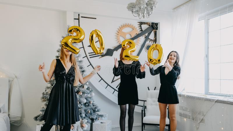 Happy girls friends holding 2020 golden balloons at New Year party, having fun together. New Year Eve 2020 party stock image