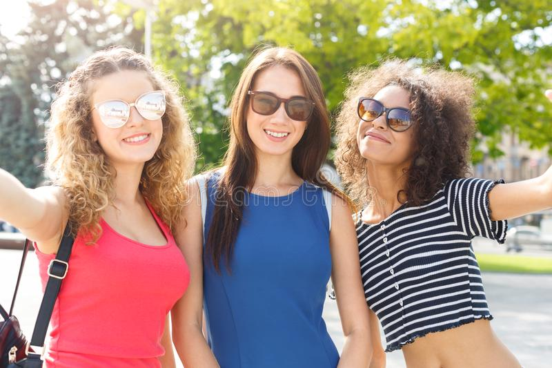 Happy girls having fun while walking in the city royalty free stock images