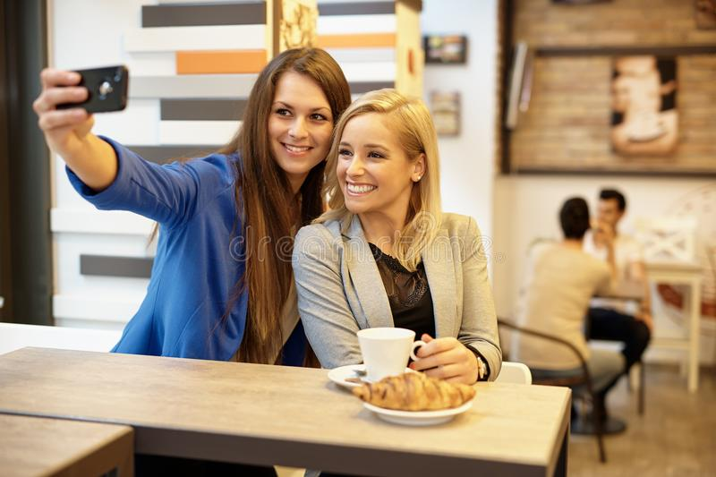 Happy girls making selfie stock photography