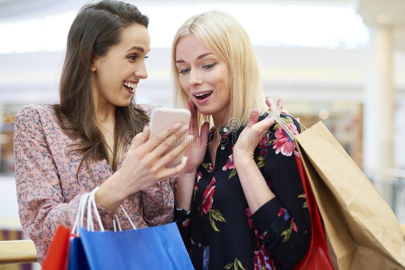 Girls with mobile phone choosing the next direction of shopping stock images