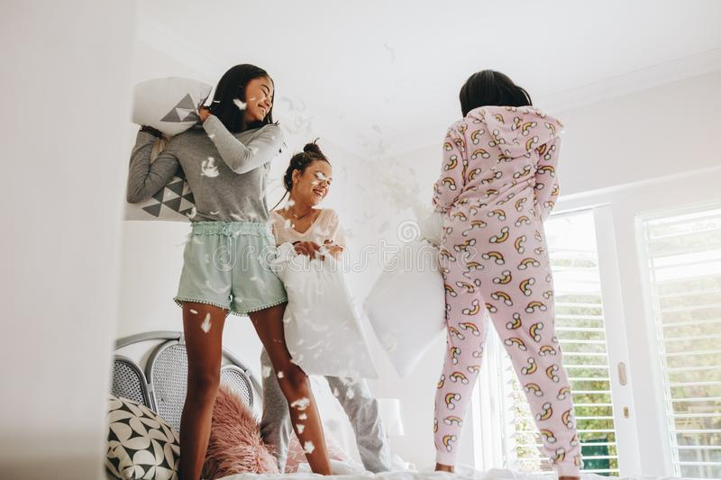 Girls pillow fighting standing on bed stock image