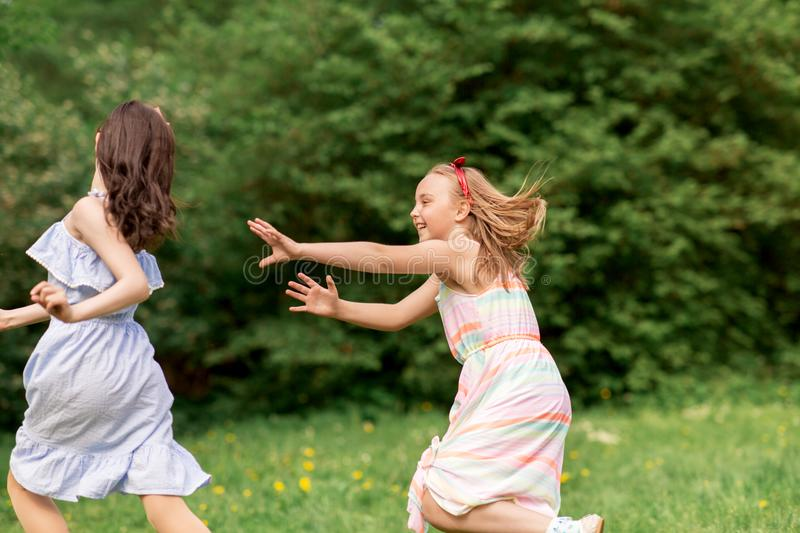 Happy girls playing tag game at birthday party. Friendship, childhood, leisure and people concept - happy girls or friends playing tag game at birthday party in stock photos