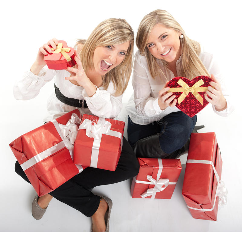 Happy girls with presents. Two young sisters surrounded by gift boxes, some of them heart shaped stock images