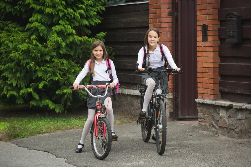 Happy young girls riding on bicycles from home to school. Happy girls riding on bicycles from home to school stock images