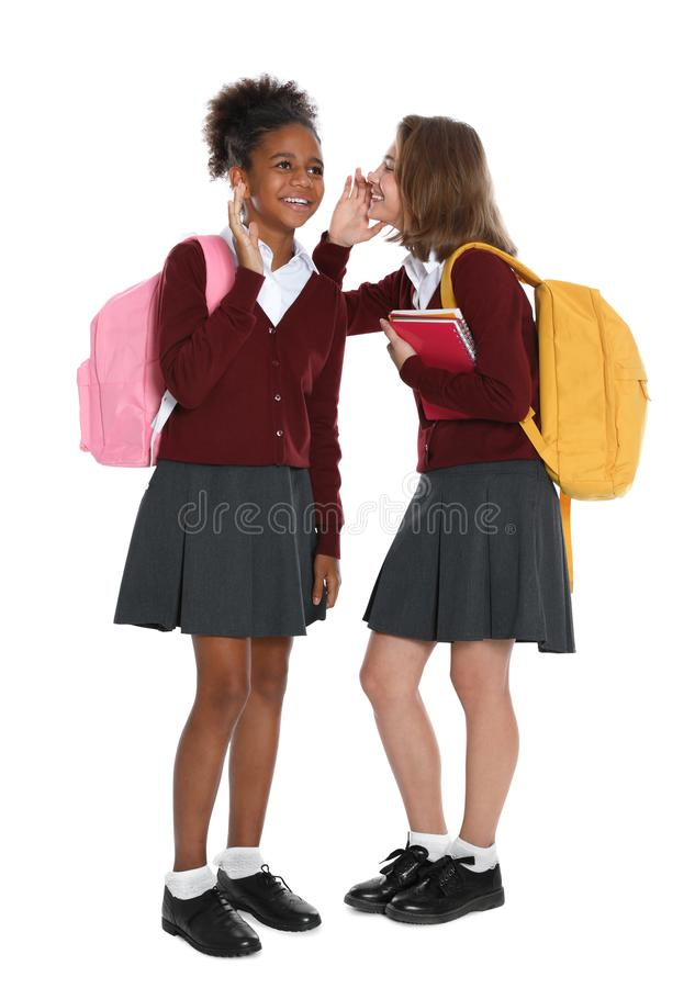 Happy girls in  uniform gossiping on white background royalty free stock images