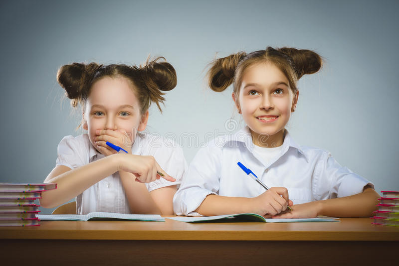 Happy girls sitting at desk on gray background. school concept royalty free stock photos