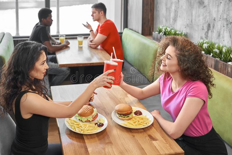 Happy girls sitting in fast food cafe, clinking paper cups. royalty free stock photography