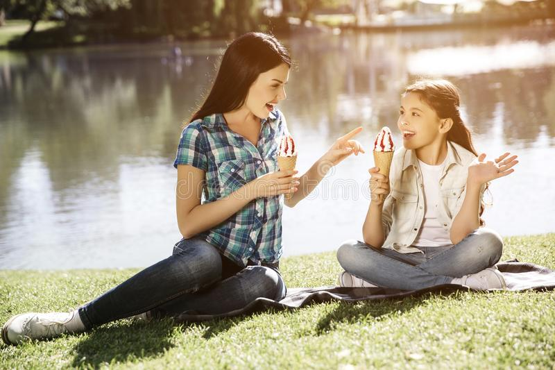 Happy girls are sitting together on grass. Young woman is reaching to her daughter`s ice cream with hand and smiling royalty free stock images
