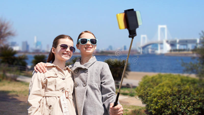 Happy girls with smartphone selfie stick in tokyo. People, children, friends and technology concept - happy girls taking picture with smartphone on selfie stick stock photography